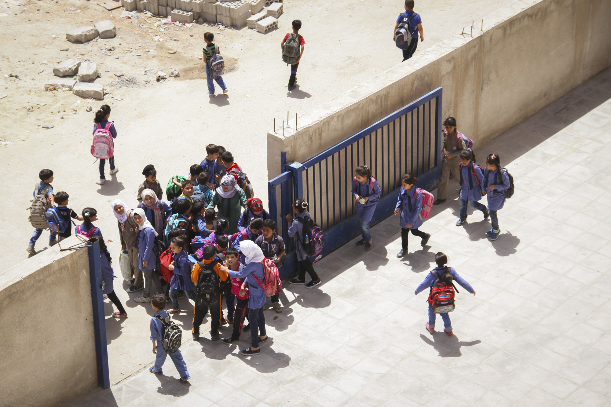 It's very busy at the gates at this time: Syrians are entering the school  to line up at the schoolyard to begin their class after the welcoming ritual. The Jordanians exit the building through the main and side entrance. At the gates carpooling Jordanian parents are waiting to pick up their children at the end of their school day.